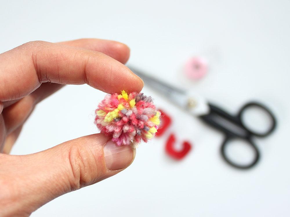 Mini-Bommel in der Hand - Teilbild der Fotoanleitung für Bommel