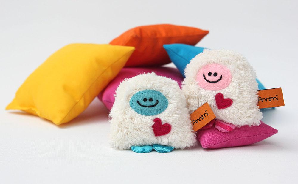 Charity-Taschenmonster in türkis und rosa auf Kissen